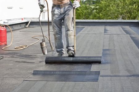 A roofer covering a roof with roofing felt