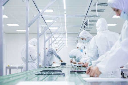 Photo pour factory workers in white lab suits and face masks, producing tv sets on a green assembly line with some modern equipment - image libre de droit