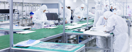 Foto de factory workers in white lab suits and face masks, producing tv sets on a green assembly line with some modern equipment - Imagen libre de derechos