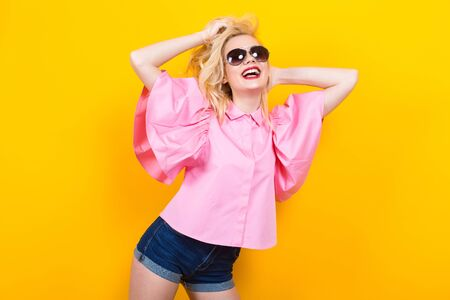 Portrait of cheerful blonde woman with red lips in pink shirt and jeans shorts with sunglasses posing on orange background with copyspace touching her hair. Fashion advertisement concept.