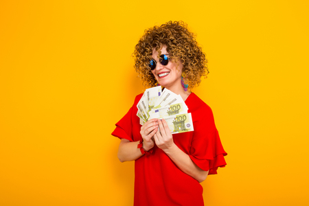 Portrait of a white happy woman with Afro hairstyle in red dress and sunglasses holding fan of euro bills isolated on orange background