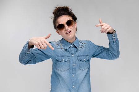 Young girl in black cat glasses on a gray background. Charming girl in a blue denim shirt.