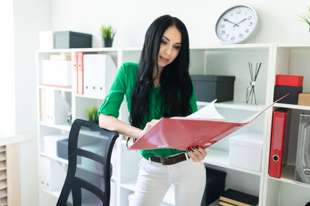 A beautiful girl in a green blouse and white trousers stands near the shelves with documents. photo with depth of field.