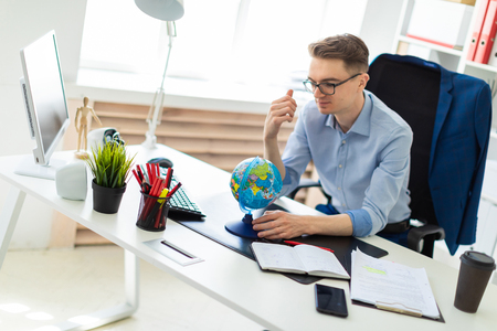 A handsome young man with glasses, blue trousers and a light shirt is working in the office. On the back of the chair hangs his jacket. photo with depth of field.