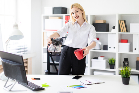 Cute young girl working in a bright office. The girl has white hair and wearing glasses. Shes wearing a white shirt and black pants. photo with depth of field
