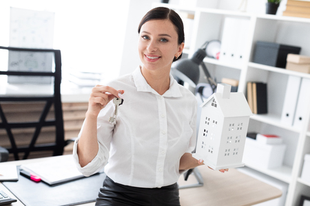 Photo pour Beautiful young girl working in a bright office. She has dark hair. Shes wearing a white shirt. photo with depth of field - image libre de droit