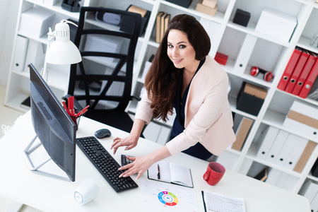 Photo pour Beautiful girl standing in a bright office. The girl is dressed in a business suit. She has long dark hair and beautiful makeup. photo with depth of field - image libre de droit