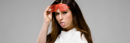 Portrait of plus size model with long hair wearing white blank T-shirt and stylish sunglasses showing her tongue with indignant look isolated on grey background with copyspace.