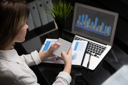 Photo pour Close-up hands holding modern calculator on chart background and laptop. Concept picture of business, market, office, tax. Close up of Business woman using calculator and laptop for do the math finance on wooden desk in office and working background in business - image libre de droit