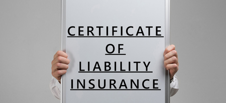 hands in a white shirt hold a banner about certificate of liability insurance isolated in a light Studio. Template-Certificate of Property Insurance. The concept of insurance and security