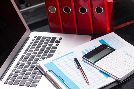Foto de Business planning office Desk with laptop and financial documents next to red folders. Can be used as a business background. Financiers workplace - Imagen libre de derechos