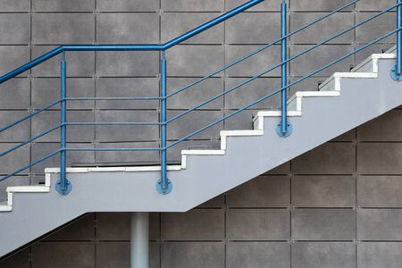 Foto de White cement stairs with blue steel railing on gray tiled wall background. - Imagen libre de derechos