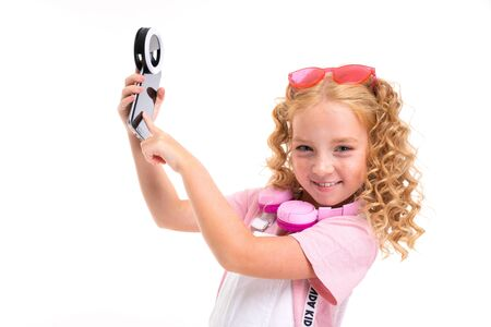 Photo pour A little girl with red heap hair in a shirt, white jumpsuit, white sneakers, pink headphones and glasses holds her phone. - image libre de droit