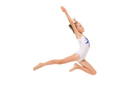 Photo for girl gymnast in white trico in full height performs in a white jump - Royalty Free Image