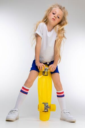 Photo for Fashion girl blonde with long hair in sports shirt, shorts, sneakers standing with yellow penny. - Royalty Free Image