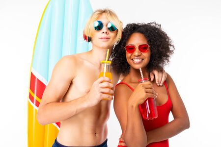 Photo pour Pretty african female and caucasian blonde man stands in swimsuit with rubber beach mattresses, drinks juice and smiles, isolated on white background. - image libre de droit
