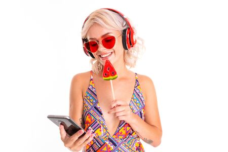 Photo pour sexy blonde girl in a swimsuit and sunglasses with a lollipop and a phone in her hands on a background of a swimming mattress. - image libre de droit