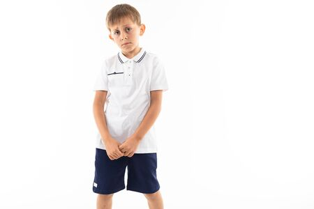 Photo for sad offended boy with bangs in a white t-shirt on a white background with copy space. - Royalty Free Image