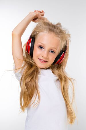 Photo for portrait of a beautiful blond charming young cute child in a casual look with red headphones listening to the music and on a white background. - Royalty Free Image