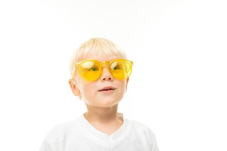 Photo pour portrait of a charming smiling blond boy in sunglasses dressed in a white T-shirt on a white studio background. - image libre de droit