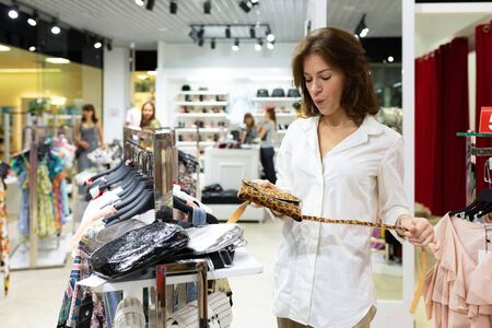 Photo pour A beautiful caucasian woman chooses a small bag in a big mall, smiles and thinks. - image libre de droit