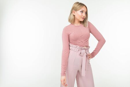 Photo pour smiling blonde girl in a pink blouse posing on a white background with copy space. - image libre de droit