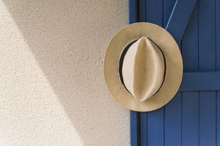 Panama hat hanging from blue wooden door