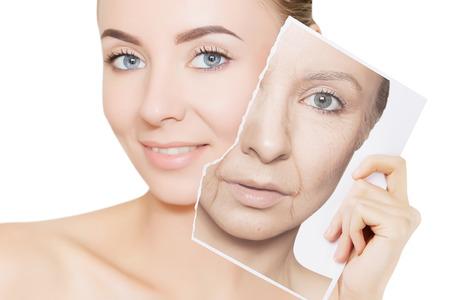 Foto de closeup portrait of young woman face holding portrait with old wrinkled face - Imagen libre de derechos