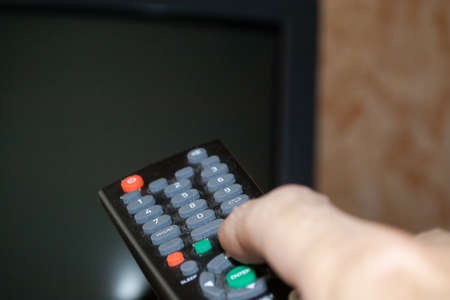 Photo pour TV remote control with buttons in a person's hand - image libre de droit