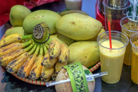 exotic fruits and freshly squeezed juice in a Cup with a straw