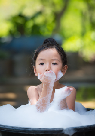 asian little girl playing with water and foam