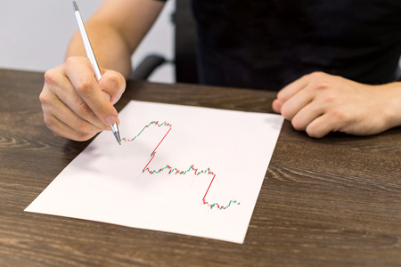 Businessman sitting at table and holds pen in right hand. There are sheet of paper with a trading chart on the table. Concept photo.