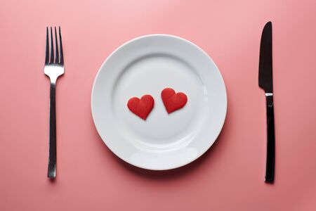 Photo pour Two hearts in plate with cutlery. Romantic dinner in restaurant concept. Meeting of lovers at wedding reception. - image libre de droit