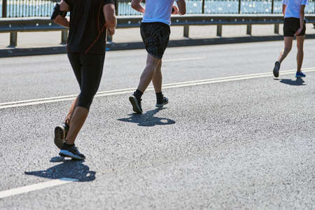 Foto de Running man. Athletic man jogging in sportswear on city road. Street marathon race, sprinting outdoor. Healthy lifestyle, fitness sport hobby. - Imagen libre de derechos