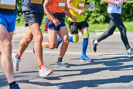 Foto de Marathon runners on city road. Running competition. Street sprinting outdoor. Healthy lifestyle, fitness sport event. - Imagen libre de derechos