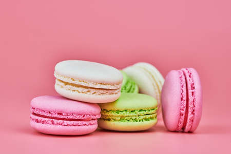 Photo pour Macaroons on pink background. Colorful small cookie from ground almonds and coconut. Popular confectionery. Tasty snack food for take away, copy space - image libre de droit