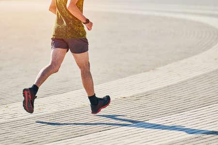 Foto de Running man. Athletic man jogging in sportswear on city road. Healthy lifestyle, fitness sport hobby. Street workout, sprinting outdoor - Imagen libre de derechos