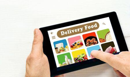 Foto de Men's hand holding tablet computer with app delivery food on screen above white desk. - Imagen libre de derechos