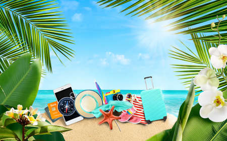 Photo for Summer tropical background of accessories for travelers on a sandy island surrounded by tropical palm leaves and flowers. - Royalty Free Image