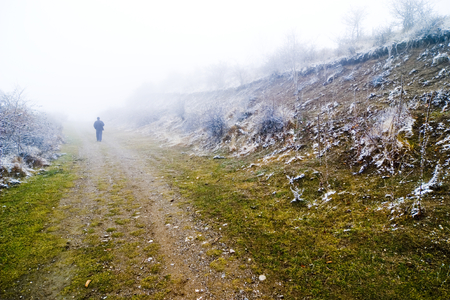 Person walking on misty pathway, lonely walk