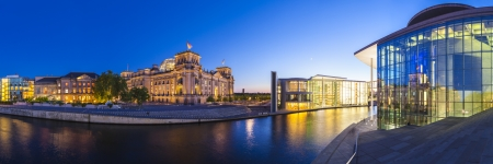 Mighty Reichstag parliament (1894), apartments and Bundeskanzleramt the German chancellery illuminated at night and reflected in the river Spree, Berlin, Germany.