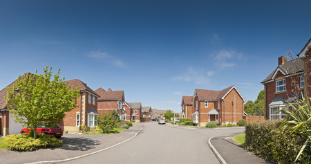 Pretty newly built homes and gardens against a clear blue summers sky  Stitched panoramic image detailed when viewed large