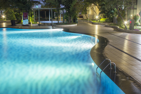 Photo pour Pool at night with lush greenery and lighting for home design and landscaping in the backyard.  Night shadows and reflections on the pool water. - image libre de droit