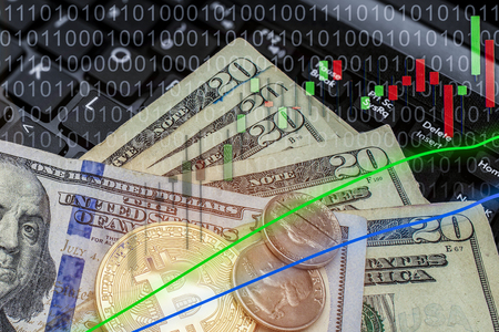 Stock exchange with money on laptop keyboard and candestick chart or graph faded in top corner.  Copy space with Bitcoin and USD currencies.
