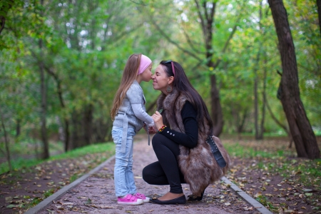 Cute little girl kissing her mother s nose