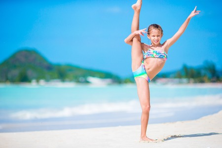Beautiful little girl on beach having fun. Happy girl enjoy summer vacation background the blue sky and turquoise water in the sea on caribbean island