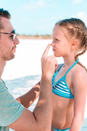 Photo pour Father applying sun cream to daughter nose. - image libre de droit