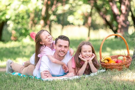 Photo for Happy father and little daughers relax by the lake - Royalty Free Image