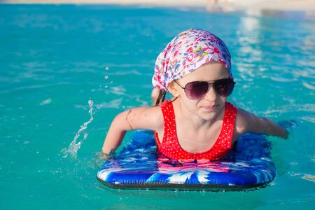 Photo pour Little cute girl swimming on a surfboard in the turquoise sea - image libre de droit