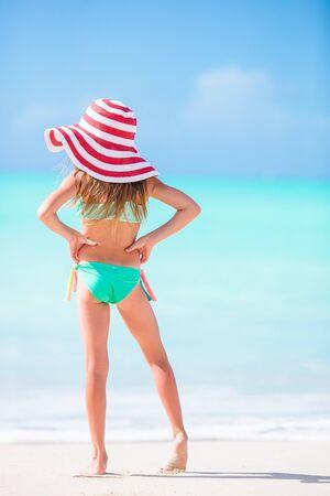 Photo pour Adorable little girl in big red hat walking along white sand Caribbean beach - image libre de droit